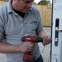 Graham Richards of St Piran's Locksmiths fixing a door lock using a drill.